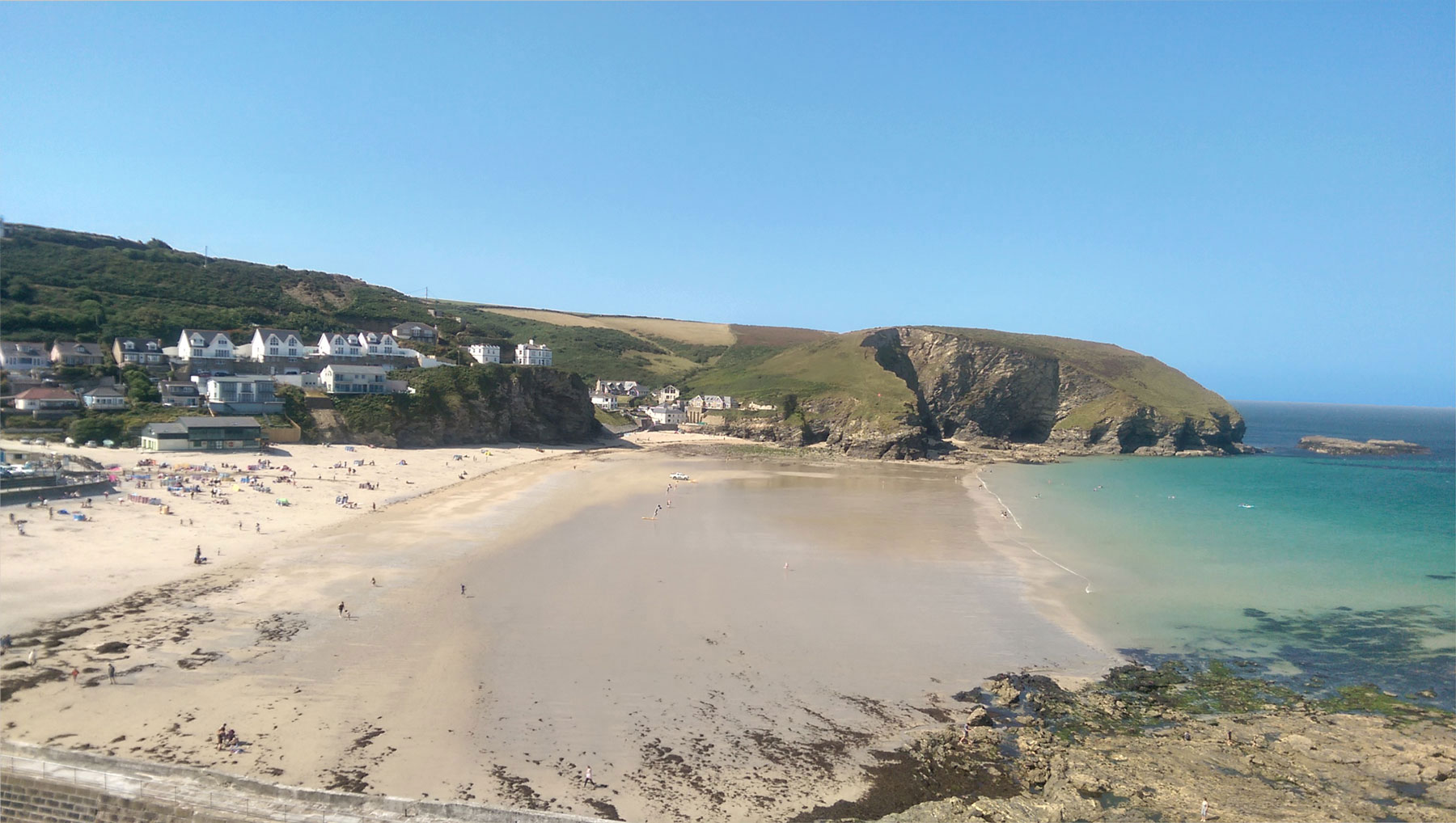 View of Portreath Beach with blue skies and clear blue water
