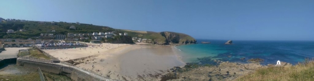 Panorama of Portreath Beach with blue skies and clear blue water