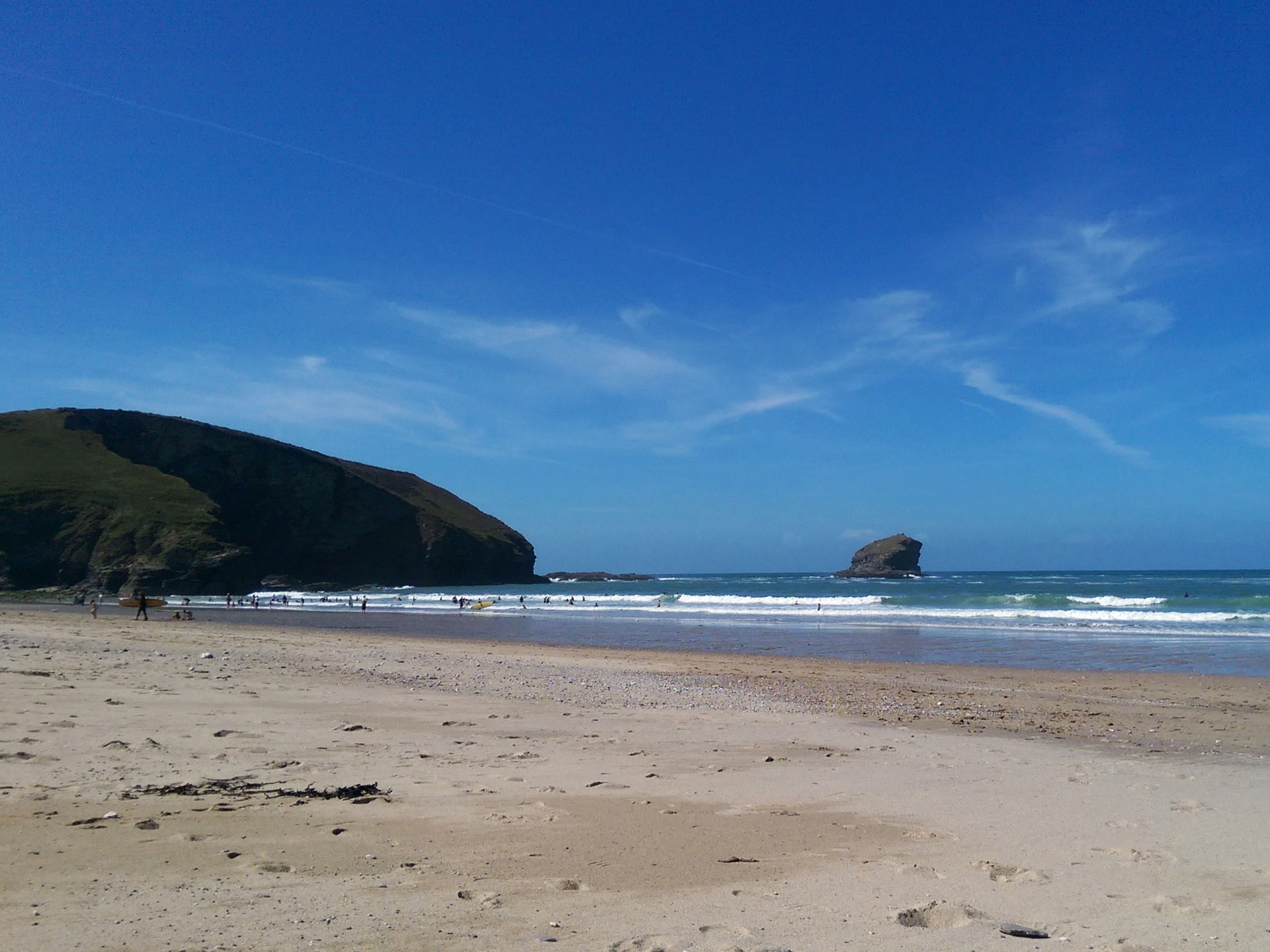 Portreath Beach with blue skies, tide out and a view of gull rock