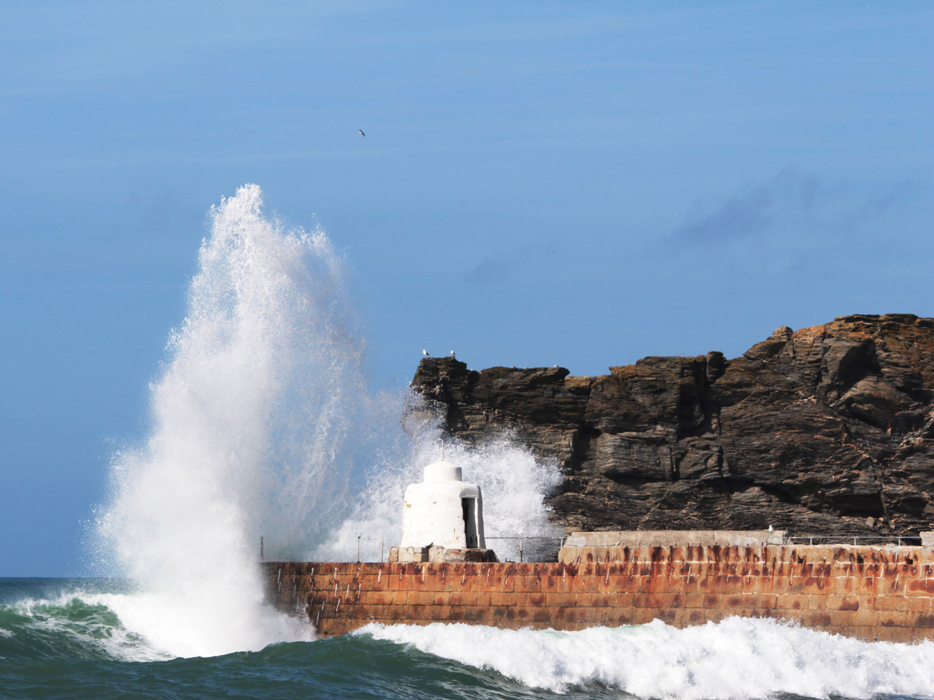 Waves crashing over the Monkey Hut on Portreath Harbour Arm