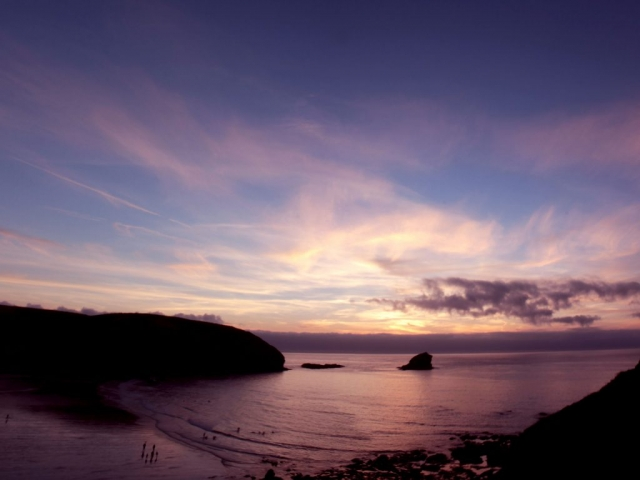 Sunset over Portreath Beach with a view over gull rock